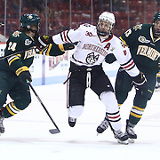 Adam Reid #8 of the Northeastern Huskies jostles for position with Chris Muscoby #24 of the Vermont Catamounts and Dan Senkbeil #13 of the Vermont Catamounts during the game at Matthews Arena on January 18, 2014 in Boston, Massachusetts. (Photo by Elan Kawesch)