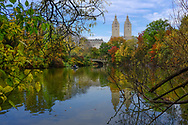 """Lakeside view from """"The Point"""" in Central Park, showing Bow Bridge and the San Remo twin towers."""