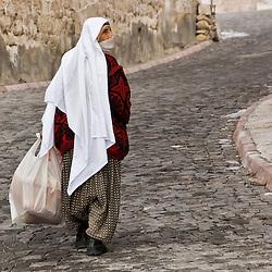 Old veiled woman walking on the streets. Capadoccia, Turkey, Asia.