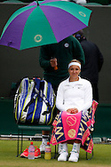 Wimbledon Championships 2012 AELTC,London,.ITF Grand Slam Tennis Tournament,.Sabine Lisicki (GER) sitzt unter dem Regenschirm und wartet,.Einzelbild,Ganzkoerper,Hochformat,schlechtes Wetter,kalt,Kaelte,