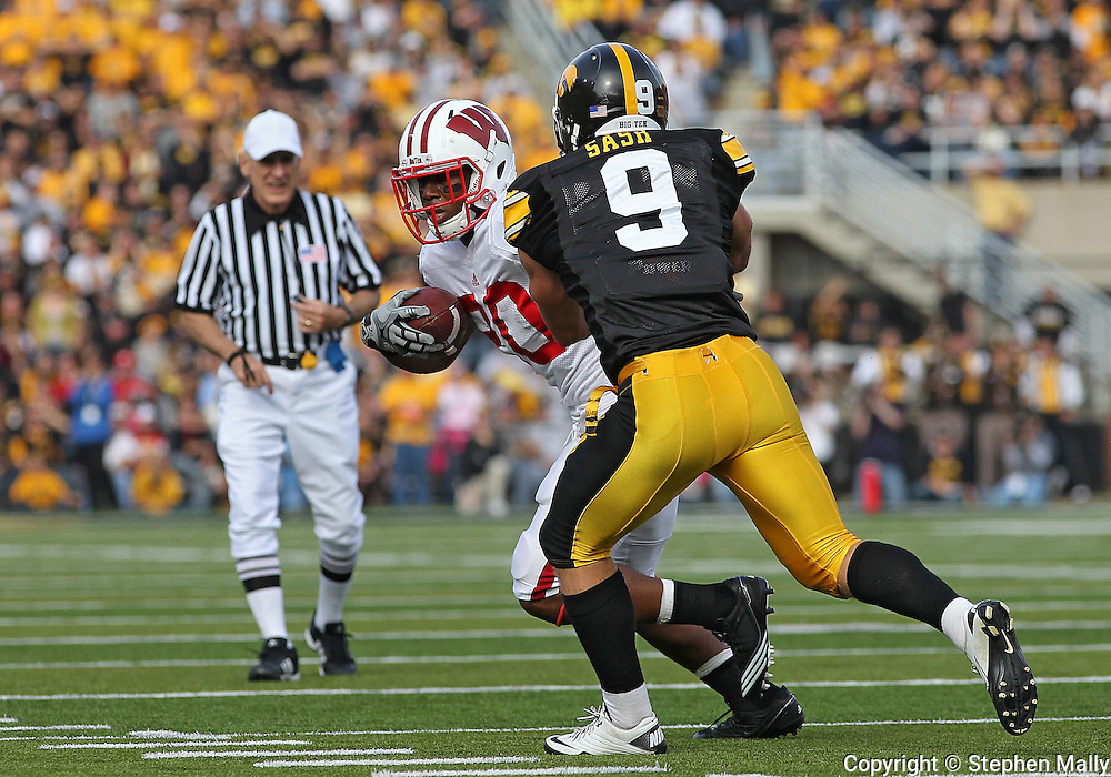 October 23 2010: Wisconsin Badgers running back James White (20) is brought down for a loss by Iowa Hawkeyes cornerback Tyler Sash (9) during the first half of the NCAA football game between the Wisconsin Badgers and the Iowa Hawkeyes at Kinnick Stadium in Iowa City, Iowa on Saturday October 23, 2010. Wisconsin defeated Iowa 31-30.