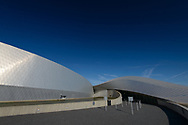 A side-angle shot of The Blue Planet Aquarium in Copenhagen, leaning towards, set against a blue sky.
