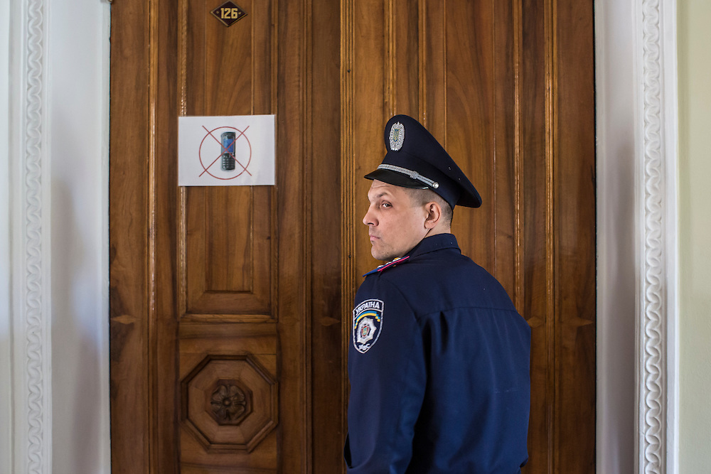 KHARKIV, UKRAINE - APRIL 24: A police officer guards the door to a meeting of the Kharkiv regional administration's legislative session as people protest outside on April 24, 2014 in Kharkiv, Ukraine. The legislative body for the Kharkiv region was being urged by pro-Russian protesters outside to schedule a referendum on greater autonomy from the central government in Kiev. (Photo by Brendan Hoffman/Getty Images) *** Local Caption ***