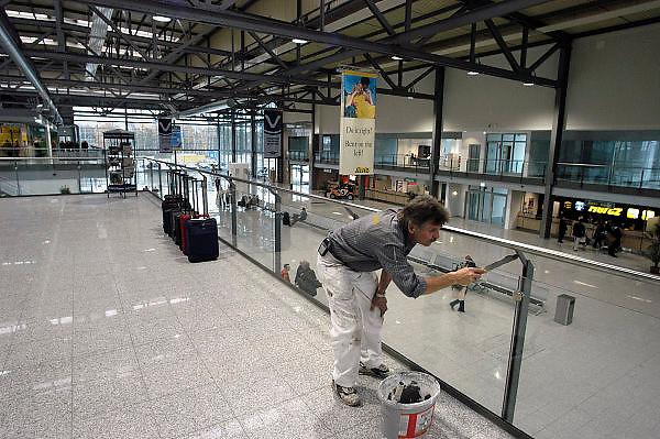 Duitsland, Laarbruch,19-11-2003..Een schilder geeft de finishing touch aan het luchthavengebouw van Airport, Flughafen, Niederrhein, van waaruit prijsvechters, chartermaatschappijen als Ryanair en VBird vliegen. Het vliegveld ligt vlak over de grens tussen Nijmegen en Venlo. Luchtvaartmaatschappij, last minute, vliegvakanties, luchtvaart, toerisme, grensstreek, economie, werkgelegenheid grensstreek. geluidsoverlast..Foto: Flip Franssen