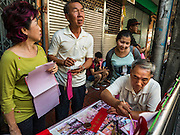 """03 FEBRUARY 2016 - BANGKOK, THAILAND:  People watch a traditional calligrapher write out New Year's greetings before Chinese New Year on Chareon Krung Road in Bangkok's Chinatown. Thailand has the largest overseas Chinese population in the world; about 14 percent of Thais are of Chinese ancestry and some Chinese holidays, especially Chinese New Year, are widely celebrated in Thailand. Chinese New Year, also called Lunar New Year or Tet (in Vietnamese communities) starts Monday February 8. The coming year will be the """"Year of the Monkey.""""            PHOTO BY JACK KURTZ"""