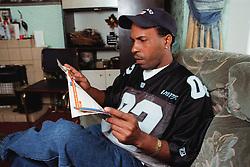 Young man wearing baseball cap sitting on sofa in lounge reading magazine,