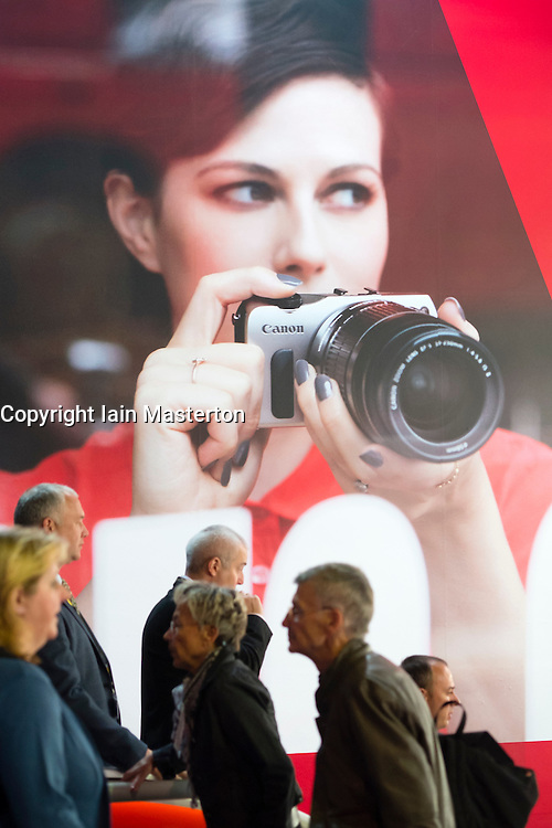 Visitors walk past large poster advertising Canon camera on second day of bi-annual Photokina photography and imaging trade fair held in Cologne Germany; Wednesday 19 September 2012