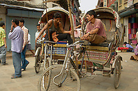 Two rickshaw drivers passing the time while waiting for riders in the old town , Kathmandu.