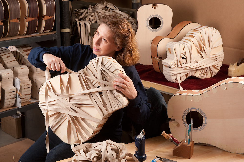 Woman handcrafting a guitar