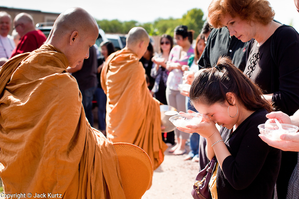 "24 OCTOBER 2010 - CHANDLER, AZ: A Thai woman bows after presenting Ajahn MAHA AMPORN with rice during the ""tak bat"" or donation of rice to the monks, an important part of Buddhist merit making, during the Ok Phansa services to mark the end of Buddhist Lent at Wat Pa, in Chandler, AZ, Sunday October 24. Buddhist Lent is a time devoted to study and meditation. Buddhist monks remain within the temple grounds and do not venture out for a period of three months starting from the first day of the waning moon of the eighth lunar month (in July) to the fifteenth day of the waxing moon of the eleventh lunar month (in October). Ok Phansa Day marks the end of the Buddhist lent and falls on the full moon of the eleventh lunar month, this year Oct 23. Wat Pa, a Thai Theravada Buddhist temple, celebrated Ok Phansa Day on October 24.    Photo by Jack Kurtz"