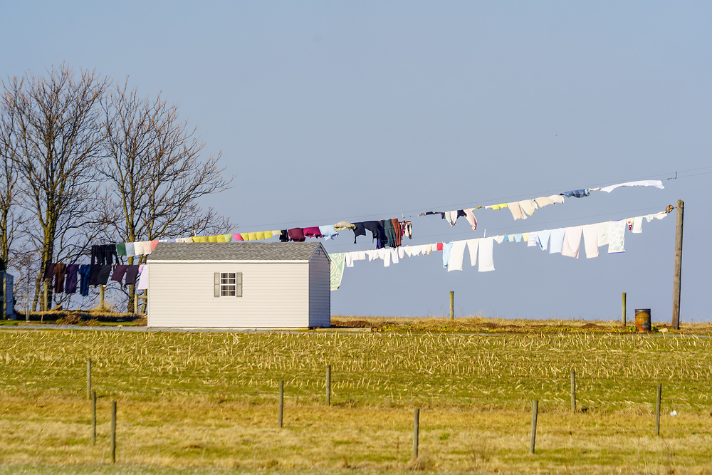 Gordonville, PA / USA - January 15, 2020: Despite cold winter weather, wash is dried outside on a long line at a typical Old Order Amish home in Lancaster County.