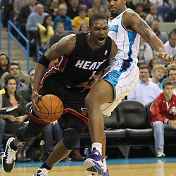 November 5, 2010; New Orleans, LA, USA; Miami Heat power forward Chris Bosh (1) drives past New Orleans Hornets power forward David West (30)during the first quarter at the New Orleans Arena. Mandatory Credit: Derick E. Hingle