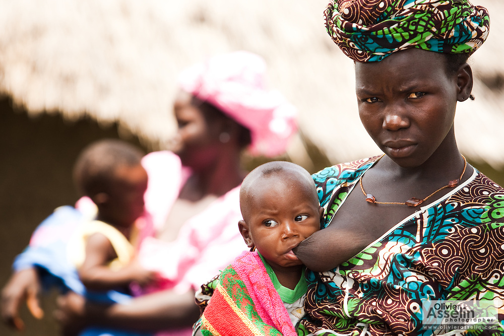A woman breast feeds her child as they wait for vaccination in the village of Banankoro, Mali on Saturday August 28, 2010.