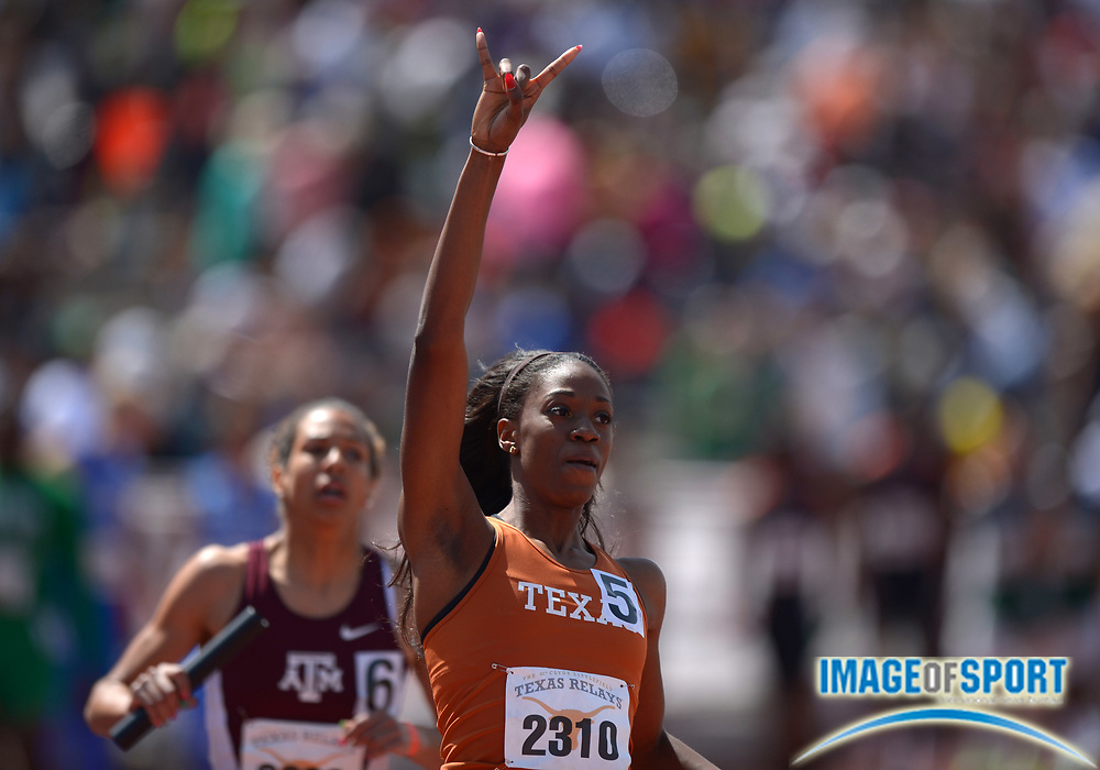 "Mar 29, 2014; Austin, TX, USA; Ashley Spencer of Texas holds up the ""Hook 'Em Horns"" sign after anchoring the Longhorns womens 4 x 200m relay team to victory in 1:31.58 in the 87th Clyde Littlefield Texas Relays at Mike A. Myers Stadium."