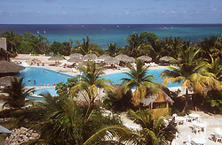 View from balcony of luxury beach resort near to Guardalavaca; Cuba; showing the pool; palm trees; and sea in the distance,