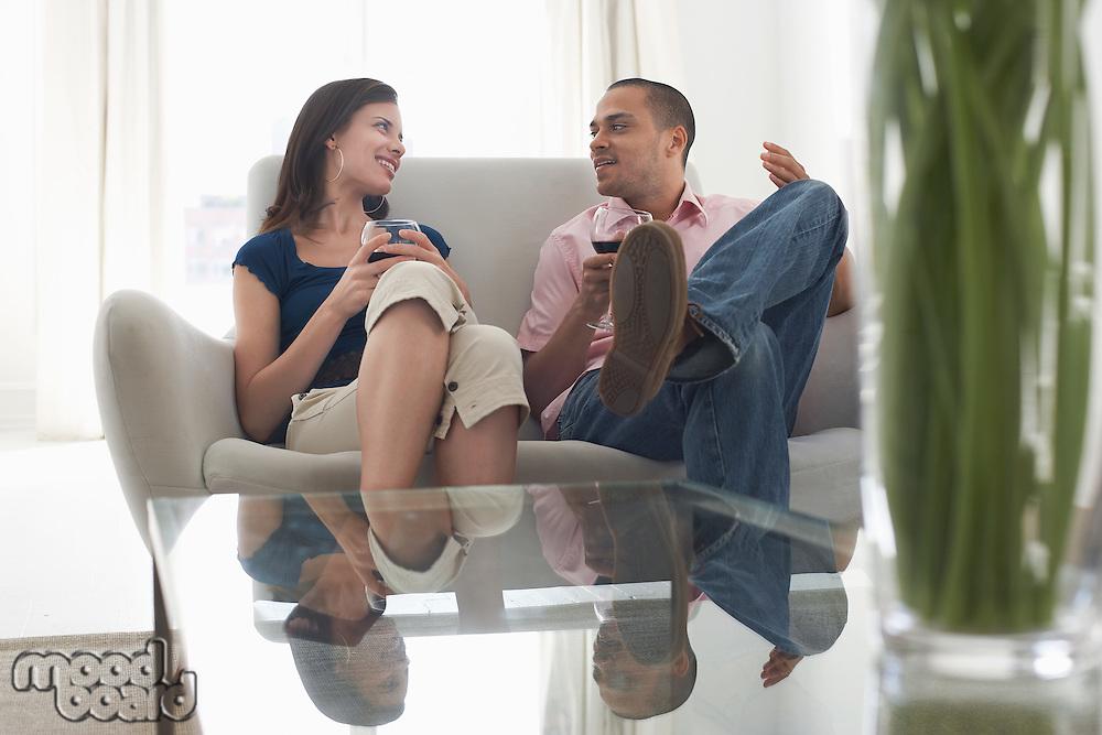 Couple drinking wine talking on sofa