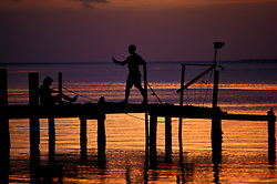Stock photo of the silhouette of two young people fishing from a pier at sunset