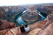 Hikers admire the view at Horseshoe Bend Colorado River Arizona USA