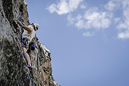 A climber with ropes scales a cliff face in Colorado Wilderness