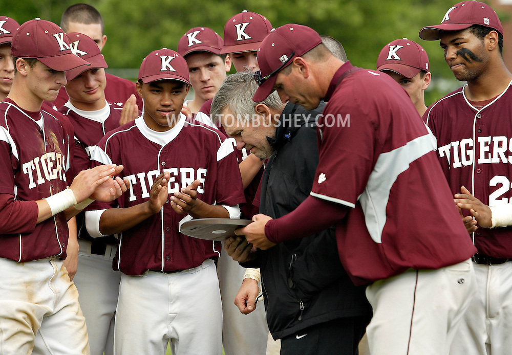 Kingston baseball coach Mike Groppuso, second from right, shows former Kingston coach Ed Mills the plaque the team won for defeating Horseheads in a state Class AA quarterfinal game at SUNY New Paltz on Tuesday, June 5, 2012.