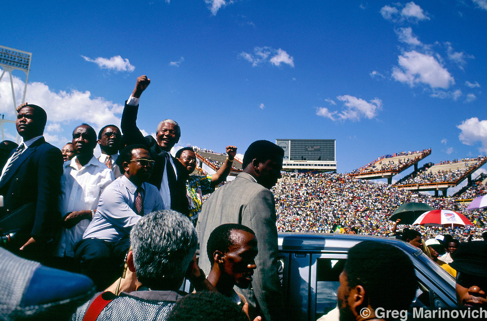 Nelson Mandela, ANC leader greets a crowd at a stadium in the Bophuthatswana homeland shortly before elections.  South Africa. 1994