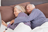 Romantic senior couple sleeping on bed at home