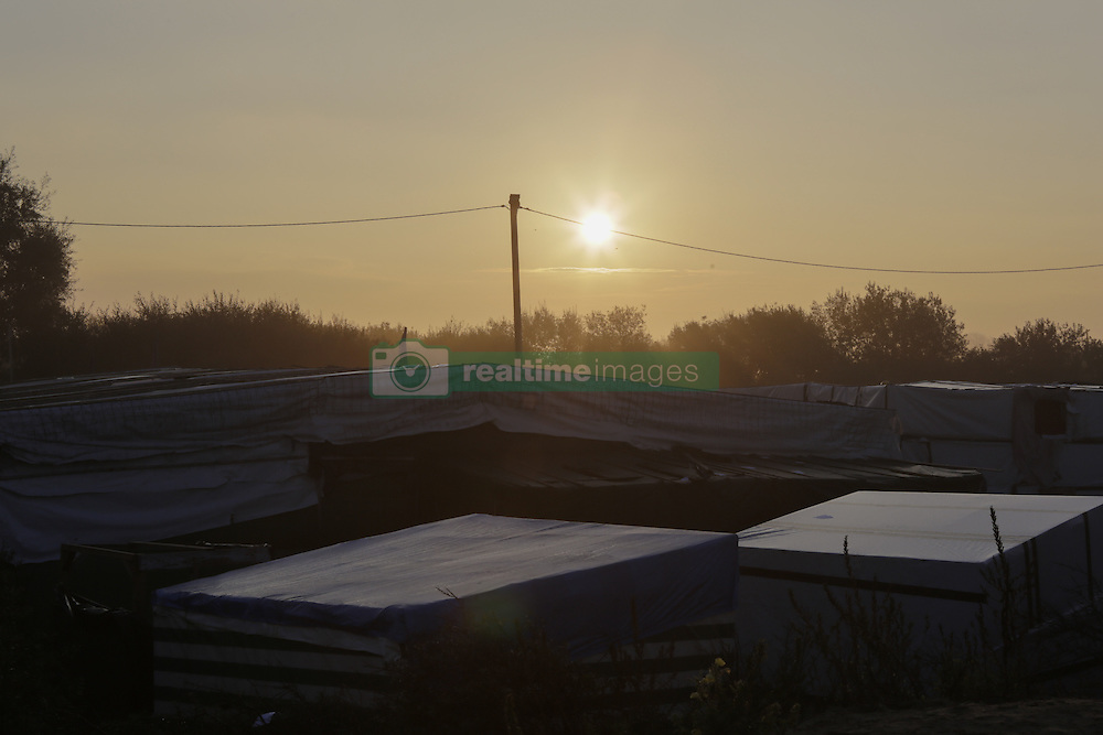 October 25, 2016 - Calais, Nord-Pas-de-Calais-Picardie, France - The sun rises over the Jungle in Calais on the second day of the eviction. A little less than 2000 refugees are expected to be disbursed from the Jungle to different areas in France on the 2nd day of the eviction of the Jungle in Calais. It is also expected that the demolition of the camp will start. (Credit Image: © Michael Debets/Pacific Press via ZUMA Wire)