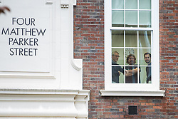 London, UK. 6 December, 2019. Members of staff look out of Conservative party HQ at a screen parked outside, supplied by campaign group Led By Donkeys, to relay broadcast journalist Andrew Neil's challenge to Prime Minister Boris Johnson to submit himself to the scrutiny of a detailed Andrew Neil interview prior to the general election, as have all other party leaders.