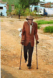 An Angolan man who lost his leg to a landmine walks several miles on crutches from a camp for internally displaced people to get food in the town of Huambo in Angola, Friday March 3, 2000. Angola's brutal 26 year-civil war has displaced around two million people - about a sixth of the population - and 200 die each day according to United Nations estimates. .(Photo by Ami Vitale)