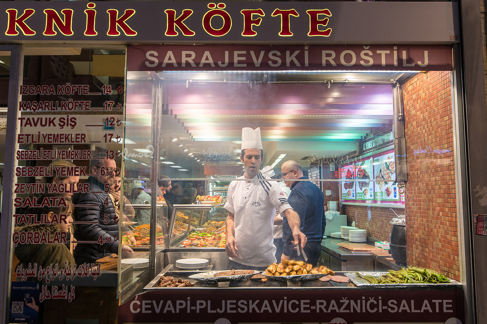 Looking through a restaurant's front window reveals an adult male chef preparing food for hungry customers,  Istanbul, Turkey