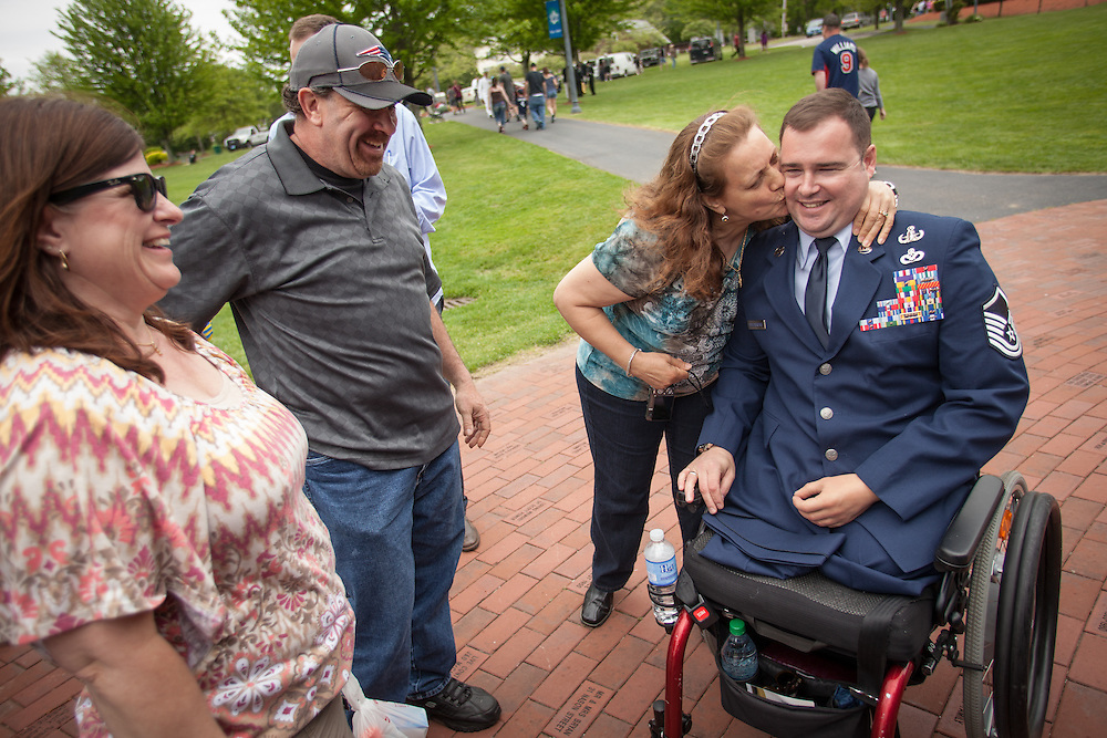 Injured Air Force Master Sgt. Joseph Deslauriers Jr. gets a kiss on the cheek from an acquaintance following Memorial Day ceremonies in his home town of Bellingham, MA on Sunday, May 19, 2013. In 2011, Deslauriers lost both of his legs and part of an arm after stepping on an explosive device while stationed in Afghanistan. He is currently rehabbing at Walter Reed Army Medical Center.  (Matthew Cavanaugh for The Washington Post)