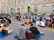 08 JUNE 2020 - DES MOINES, IOWA: People sit in the middle of Robert D. Ray Drive and listen to the Des Moines City Council debate a racial profiling ordinance on a Zoom call. About 150 people staged a sit-in in front of the Des Moines City Hall Monday afternoon and listened to the City Council debate an ordinance about racial profiling. The sit-in was organized by Des Moines' Selma, a civil rights organization based in Des Moines. Des Moines' African-American community has sponsored and coordinated a series of events to draw attention to police violence in Des Moines in the wake of George Floyd's death at the hands of Minneapolis police.      PHOTO BY JACK KURTZ