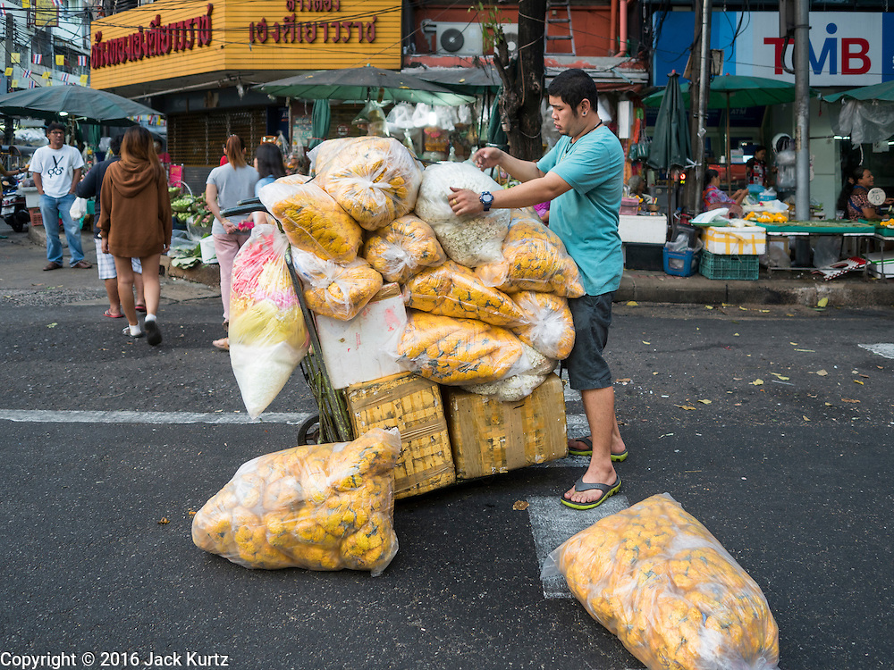 24 FEBRUARY 2016 - BANGKOK, THAILAND: A porter delivering marigolds used to make flower garlands picks up his cargo after his handtruck tipped over at Pak Khlong Talat. Bangkok government officials announced this week that vendors in Pak Khlong Talat, Bangkok's well known flower market, don't have to move out on February 28. City officials are trying to clear Bangkok's congested sidewalks and they've cracked down on sidewalk vendors. Several popular sidewalk markets have been closed in recent months and the sidewalk vendors at the flower market had been told they would be evicted at the end of the month but after meeting with vendors and other stake holders city officials relented and said vendors could remain but under stricter guidelines regarding sales hours. The flower market is one of the best known markets in Bangkok and has become a popular tourist destination.        PHOTO BY JACK KURTZ
