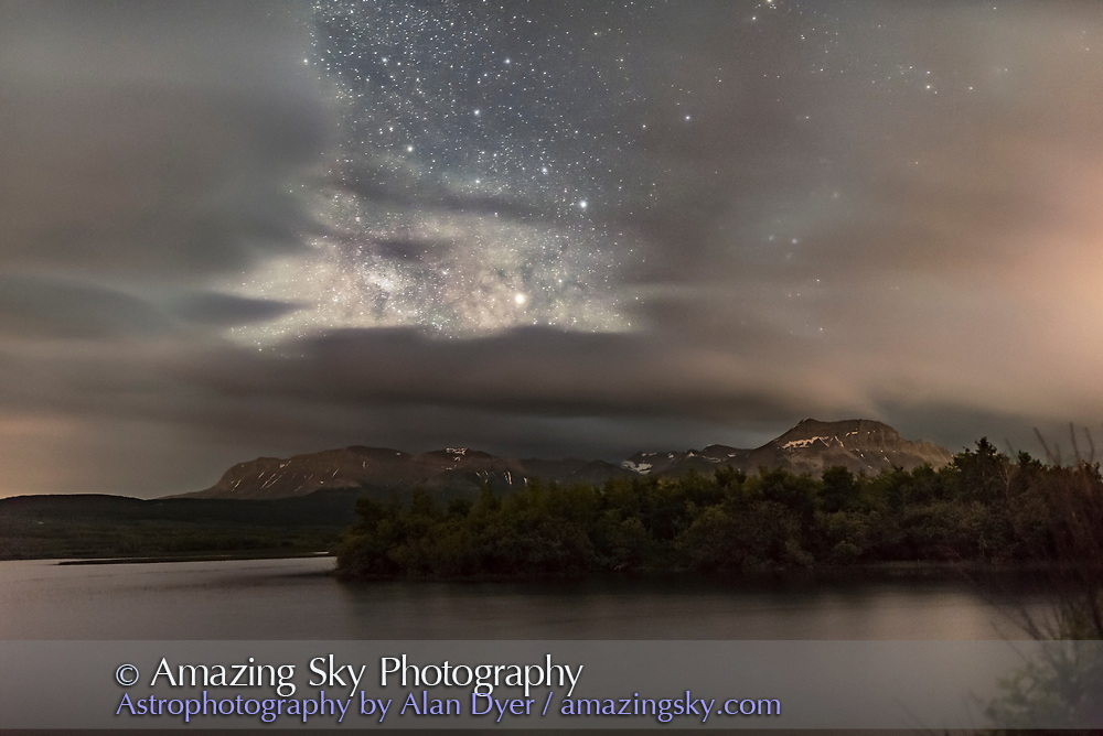 Saturn (the bright object at centre) at opposition and brightest for the year on June 15, 2017, over Maskinonge Pond at Waterton Lakes National Park, and shining amid clouds and the Milky Way. <br /> <br /> I shot this at one of my annual Workshops at Waterton, on a cloudy night but with some clear breaks now and then. This is a stack of 5 x 25-second exposures for the ground, mean combined to smooth noise, and one 25-second exposure for the sky, all at f/2 and ISO 4000, with the Sigma 24mm lens and Nikon D750.