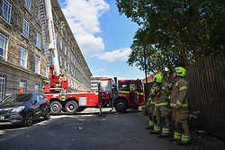 © Licensed to London News Pictures. 16/07/2019. London, UK.  Multiple fire engines respond to a fire in a residential block on Bromyard Avenue, in Acton, West London. A black plume of smoke was visible for miles as the penthouse apartment burned. Police helicopters, LBF drones, and paramedics were on the scene in minutes. It is not known at this stage if there were any casualties.  Photo credit: Guilhem Baker/LNP