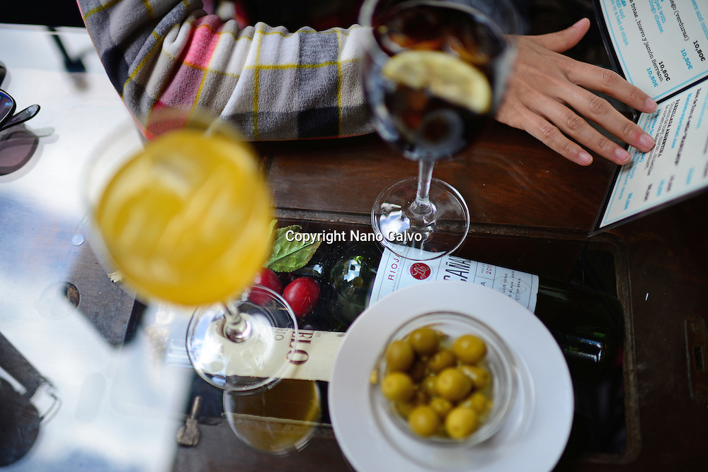Woman checks menu while eating aperitif at restaurant, Granada, Spain