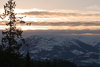 Cloud layers catch the orange light of sunset over the Tantalus Range, as seen near Whistler, BC Canada