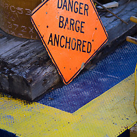 A danger anchored barge sign sitting on a barge on the east river new york city