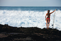 Hawaiian landscape with beautiful female surfer in bikini posing on lava rocks.