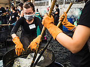 04 NOVEMBER 2016 - BANGKOK, THAILAND:  Volunteers put clothes to be dyed black into a tub of dye at Krungthai Tractor. About 150 volunteers are working at Krungthai Tractor in Bangkok to dye clothes black for people in mourning following the death of Bhumibol Adulyadej, the King of Thailand. The government declared a one year mourning period, during which Thais are encouraged to wear black and a 30 day mourning period during which Thais are very strongly encouraged to wear black. Furthermore, black is mandatory for official mourning functions, including visits to the Grand Palace and Sanam Luang, the public ceremonial ground across the street from the Palace. The expectation to wear black created a shortage of black clothes in many markets and Thailand's poor couldn't afford what black clothes were still available. Community groups have started dyeing clothes for people who either can't find or can't afford black clothes. The clothes dyeing volunteers at Krungthai Tractor were organized by Thai actress Chompoo Araya A. Hargate and Thai fashion blogger Chavaporn Laohapongchana.     PHOTO BY JACK KURTZ