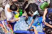 14 APRIL 2013 - BANGKOK, THAILAND:  People load their water guns from a cooler chest full of water on April 14, 2013 in Bangkok, Thailand. The Songkran festival is celebrated in Thailand as the traditional New Year's Day from 13 to 15 April. The throwing of water originated as a way to pay respect to people and is meant as a symbol of washing all of the bad away. PHOTO BY JACK KURTZ