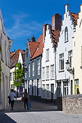 Couple walking past traditional architecture painted houses with crow-stepped gables by Peerdenstraat and Groenerei (green Canal) in Bruges, Belgium