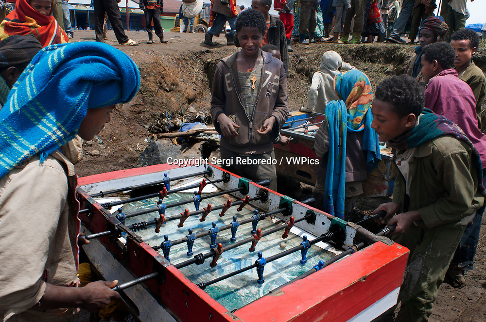 Market place. Debark. Simien Mountains. Northern Ethiopia. Debark Market. Several children play foosball while their parents are selling or buying.<br /> The village of Debark is the starting point towards the Simien Mountains one of the wonders of Ethiopia. Here they meet to buy and sell their products, the market is the heart of the village, the center of this small world. Sewing machines of which your grandmother used to sell clothes, shoes, wool and an endless number of other things, it is a world of smell and color.