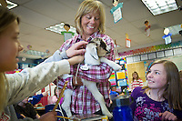 Sydney Bybee, left, and Mallory Michaels, both 11, pet a baby goat as Sharyl Rasmussen, a teacher at Hayden Elementary School, escorts the kid through her classroom Monday after receiving the barnyard animal from her student, Samantha Schoenfeld. The goat was delivered by volunteers with the Wishing Star Foundation as a fundraiser for the organization in which goats are delivered to people who have to pay to have the farm animals taken away. Information: www.sendafriendagoat.com