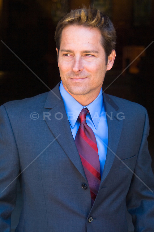Portrait of confident business man in a gray/ blue suit and red striped tie