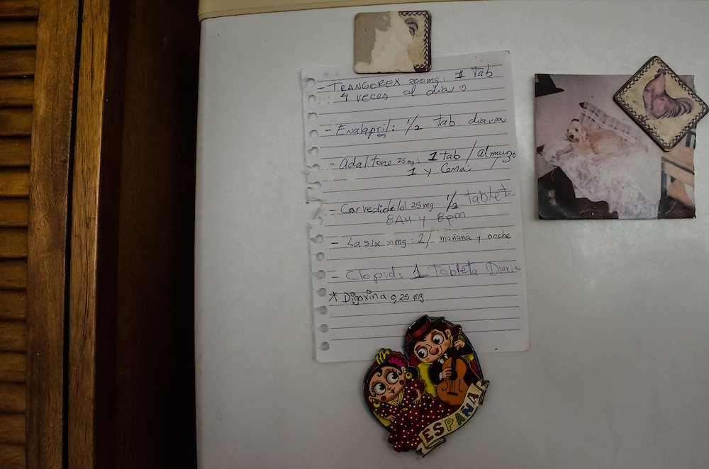 CARACAS, VENEZUELA-JANUARY 22, 2015: A handwritten note hangs on the refridgerator of all the pills Ignacio Ortiz, 72,  needs to take for his heart condition.  His family has not been able to find Digoxina for 3 months. His daughter said sometimes, she has to pay a bribe to workers under-the-table at the government-run socialist pharmacy to  sell her hard to find medicines, or buy them on the blackmarket for 4,000 bolivares for a months supply --100 times the official government price, and her entire month's paycheck.  She blames the government for the economic crisis, and subsequent shortages, and believes that if she is unable to find the medicine her father needs, that he will die soon.