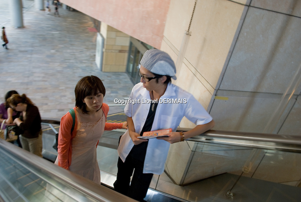 Couple in escalator in Roppongi Hills, Tokyo, Japan.