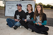 June 1, 2015, Denton, Texas, Adam Briggle Tara Linn Hunter  and Niki Chochrek, members of the Denton Drilling Awareness Group in front of a Vantage Energy fracksite. . Three members of the Denton Drilling Awareness Group were arrested when they refused to move away from the entrance to a fracking site where work began on June 1 despite a fracking ban the citizens of Denton voted for seven months ago.  Texas Governor Greg Abbott signed legislation, HB 40, that prohibits cities and towns in Texas from banning fracking