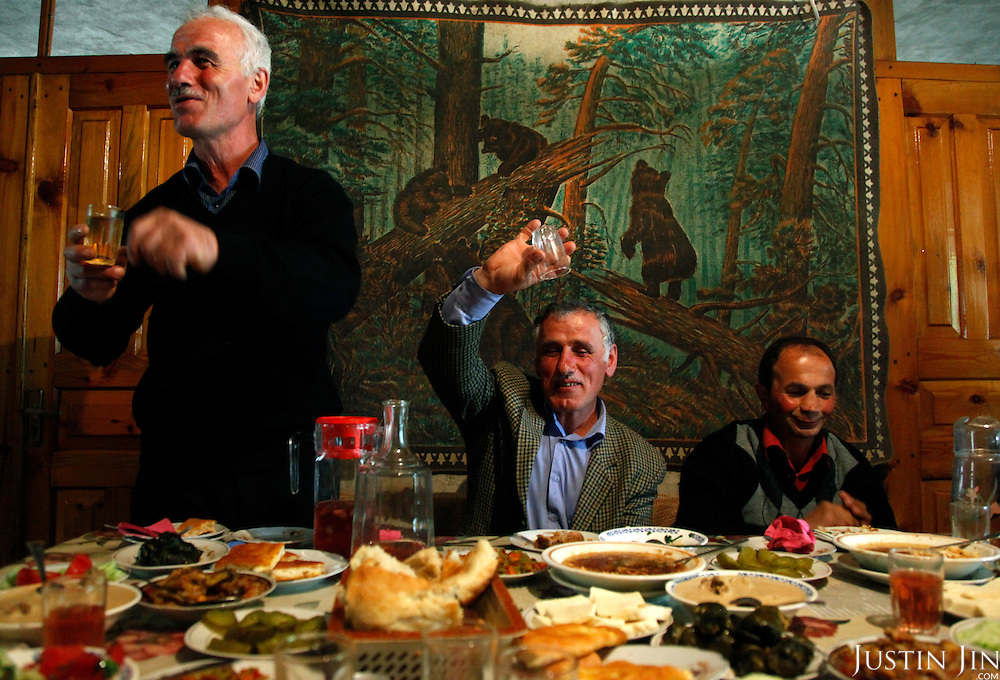 Men and women drink and eat at a village home in Keda, Georgia, on the mountainous border with Turkey.