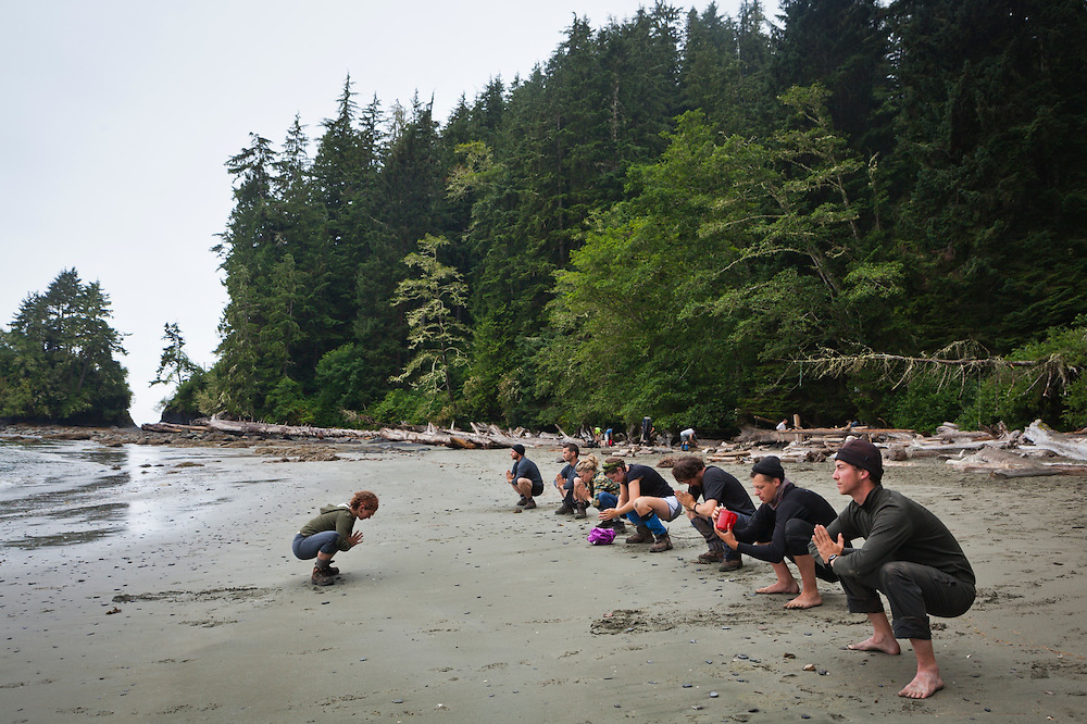 Hikers do morning yoga on the beach at Thrasher Cove, West Coast Trail, British Columbia, Canada.